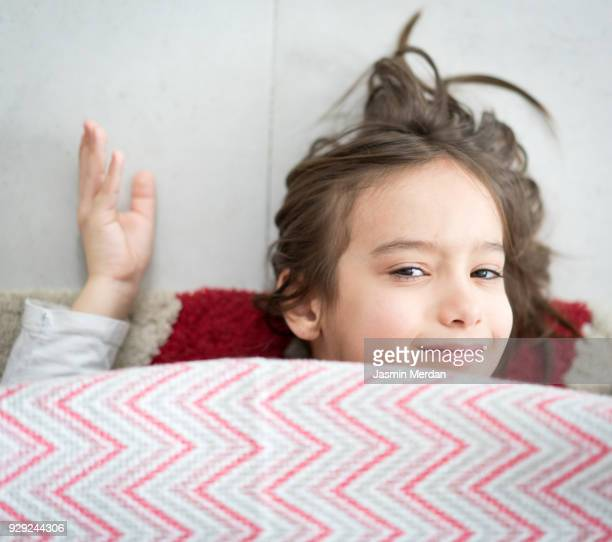 Child in a pillows and chairs fort making home