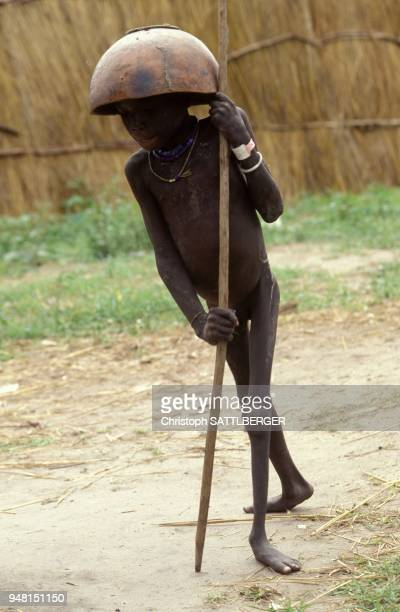 Child in Ayod wearing his food bowl as hat