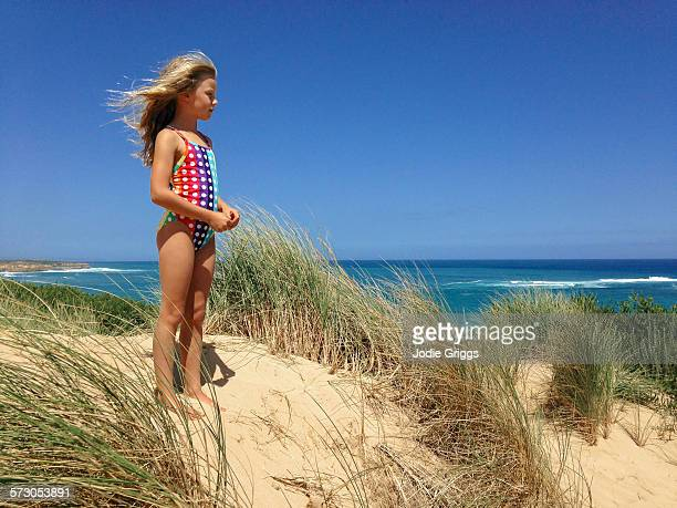 Child in bathing suit standing on large sand dune