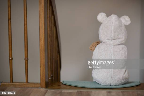 Child in bear pyjamas, sitting alone on stairs at bedtime