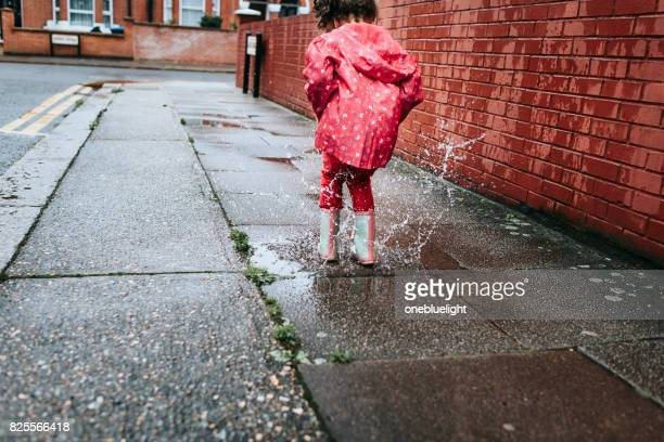 child (5-6) in blue boots jumping in puddles. - onebluelight stock pictures, royalty-free photos & images
