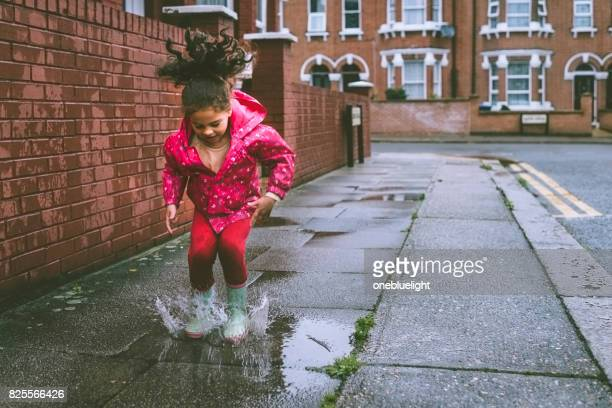 child (5-6) in blue boots jumping in puddles. - puddle stock pictures, royalty-free photos & images