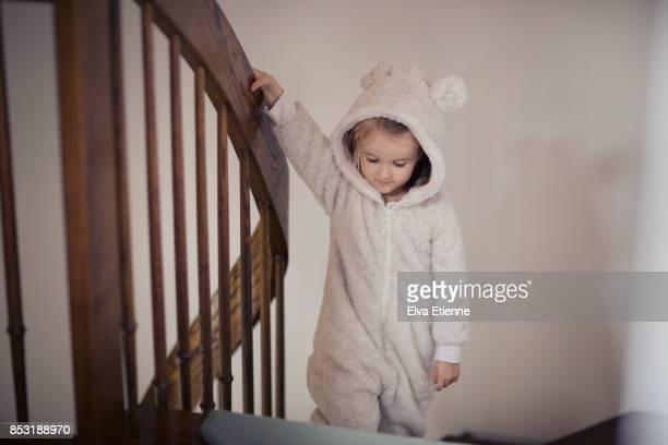 Child in cozy pyjamas, walking upstairs at bedtime