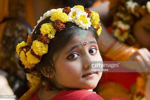 A child in festive dress on the cultural program organized by students of Fine Art Institute of Dhaka University marking Basanta Utsav the festival...