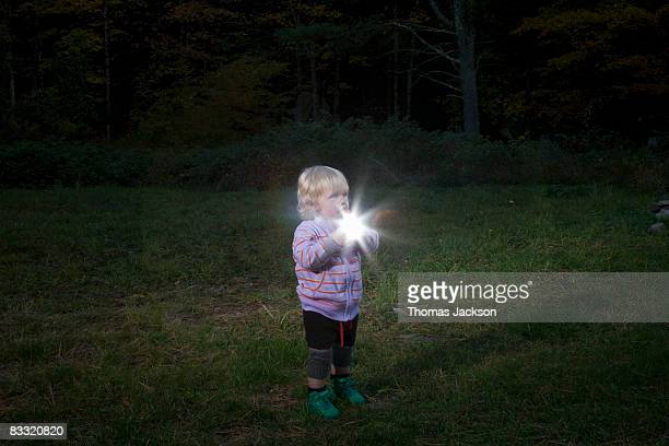 Child in field holding light