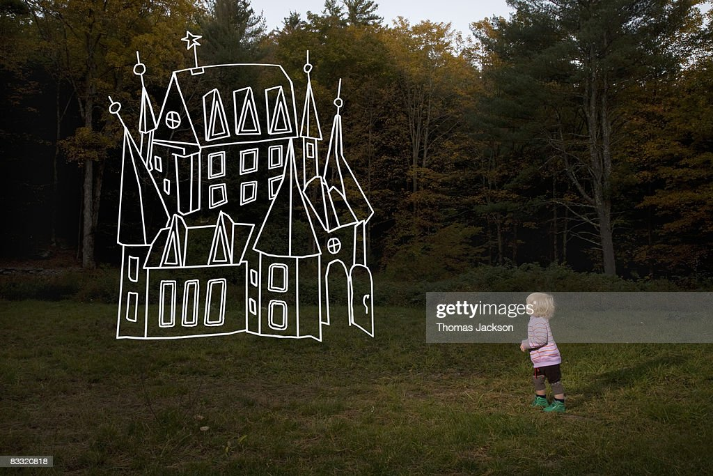 Child in field looking at imaginary house