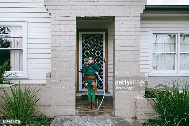 Child in front of house in Robin Hood costume