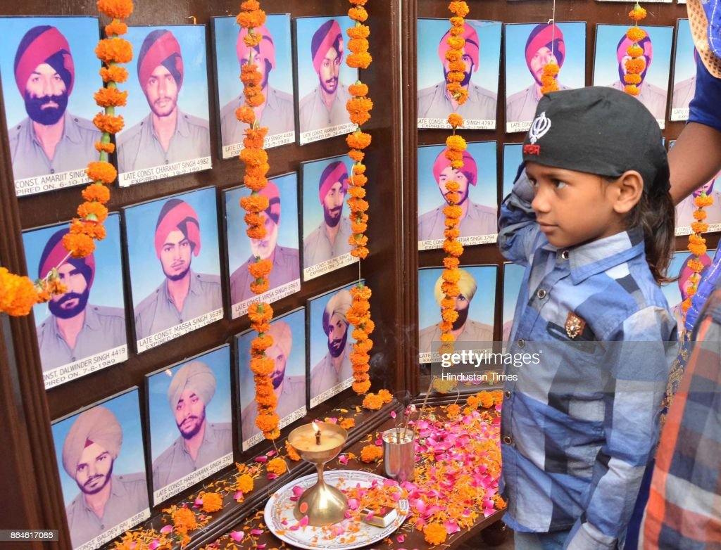 A child in front of the portraits of martyrs during an annual Police Commemoration Day at Amritsar Rural Police Line at Daburji on October 21 2017 in.
