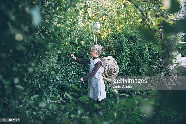 Child in garden wearing home-made snail costume