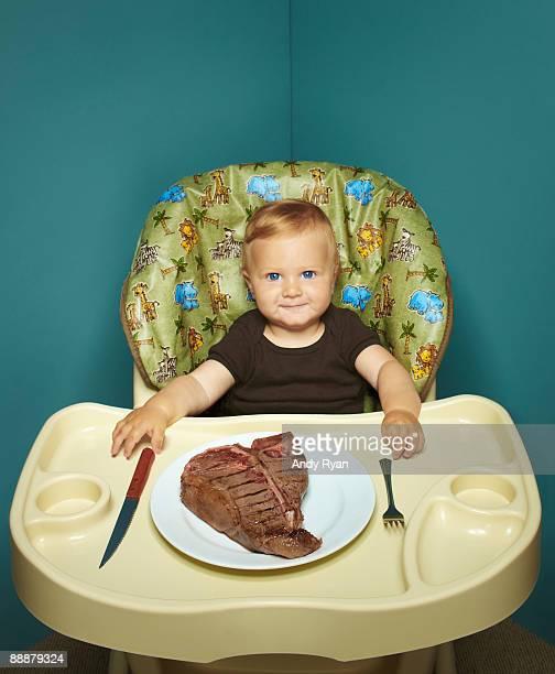 Child in high chair with T Bone steak.
