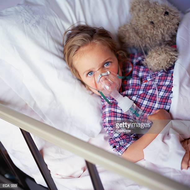 Child in hospital bed, wearing oxygen mask, holding stuffed animal