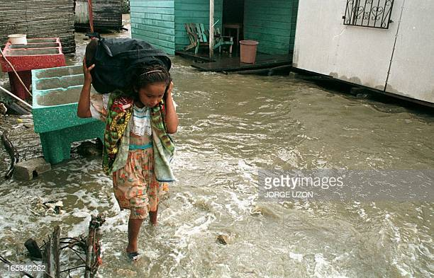 A child in in Puerto Barrios 295kms north of Guatemala City carries some of her belongings as people in the area evacuate their homes flooded by an...