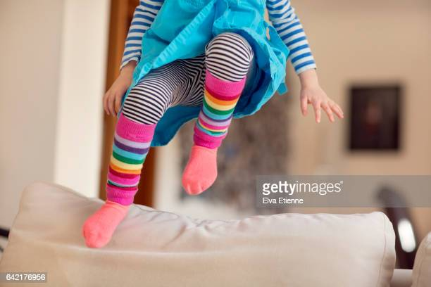 Child in mid-air, jumping onto a sofa