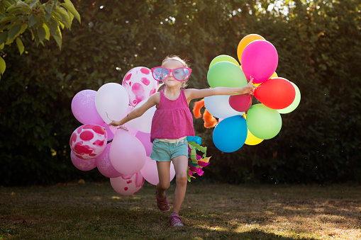 Child in novelty glasses, pulling multi coloured balloons acround a back yard - gettyimageskorea