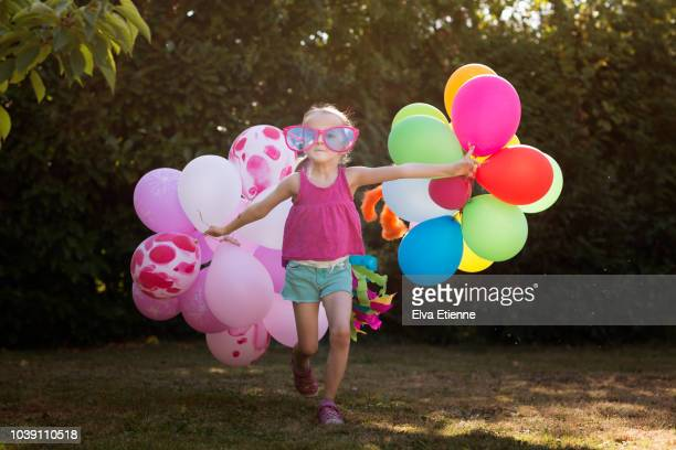child in novelty glasses, pulling multi coloured balloons acround a back yard - offbeat stock pictures, royalty-free photos & images