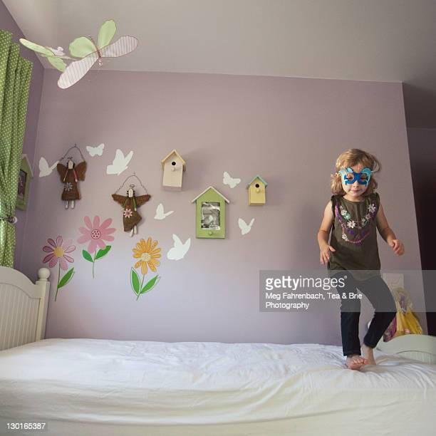 Child in party mask is playing on empty bed