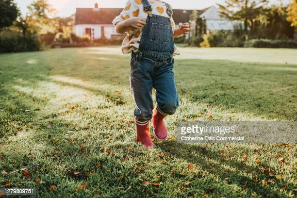 child in pink welly boots on grass - weather stock pictures, royalty-free photos & images