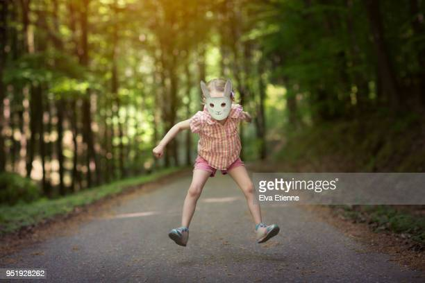 child in rabbit mask jumping on a forest path - easter mask stock pictures, royalty-free photos & images