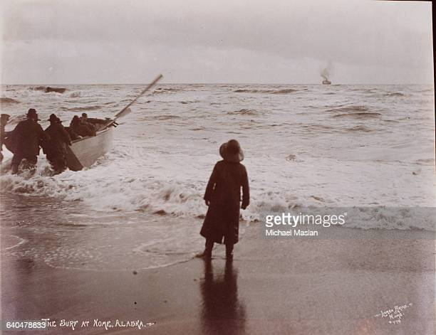 Child in rain gear watches from the surf's edge at Nome as a group of men struggle to launch a rowboat.