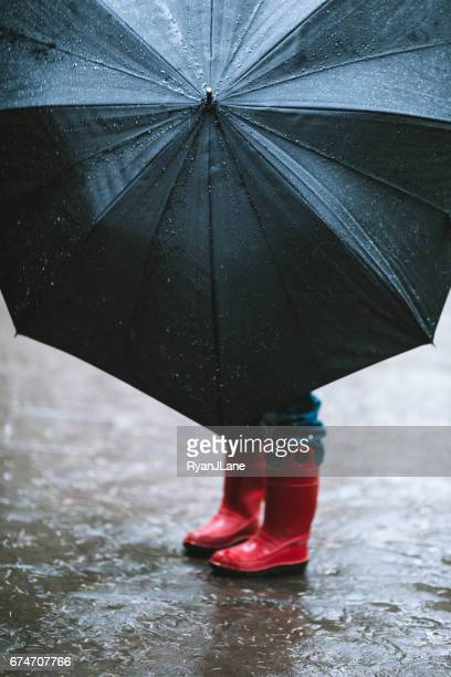 傘と雨の中で子 - 赤のブーツ ストックフォトと画像