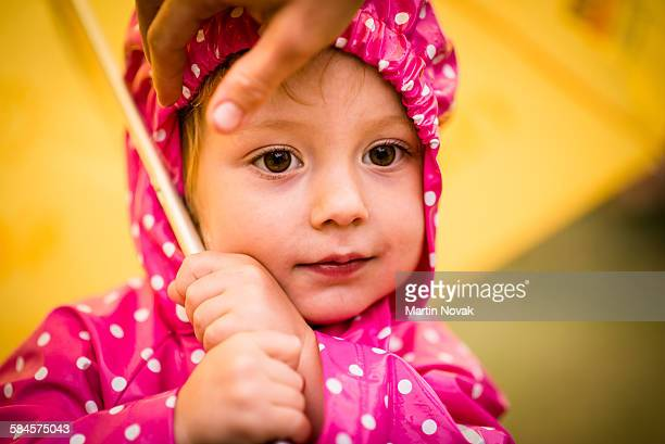 Child in raincoat with umbrella