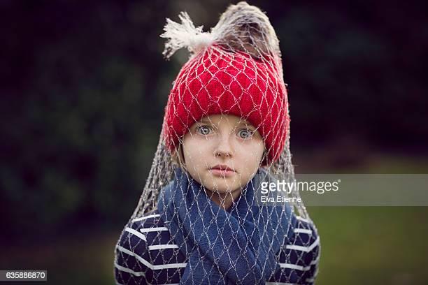 child in red bobble hat wrapped in plastic netting - junge gefesselt stock-fotos und bilder