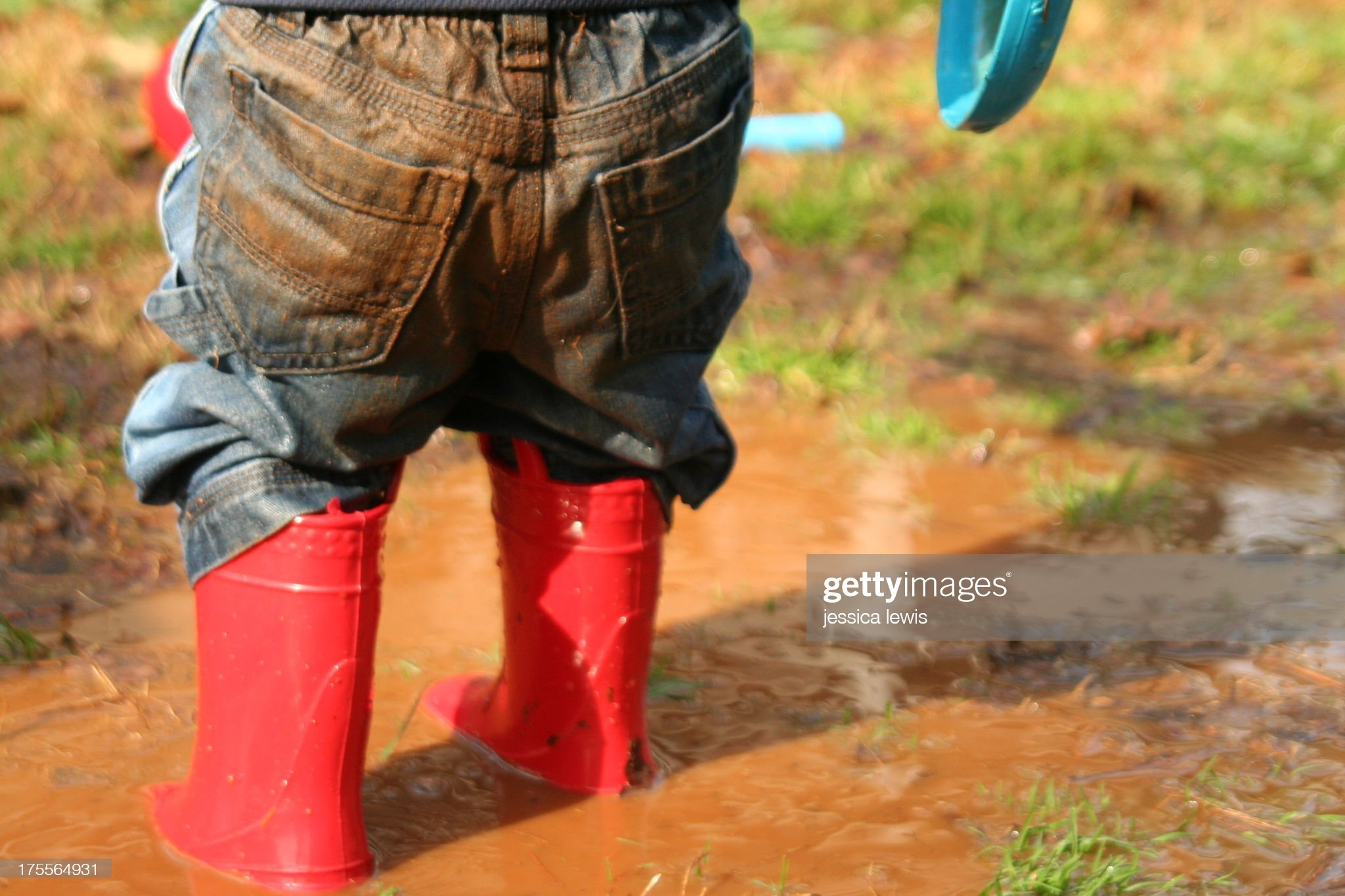 child in red boots standing in mud puddle : Stock Photo