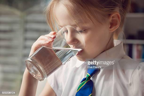 Child in school uniform drinking water