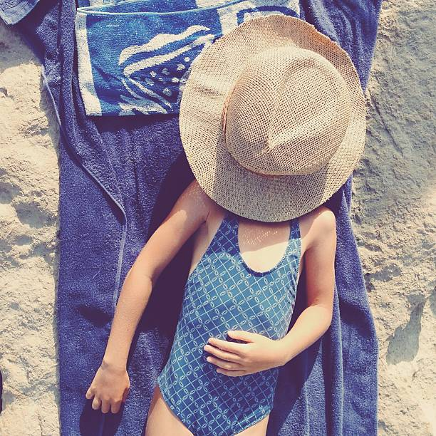 Child in swimsuit laying on towel with sun hat on