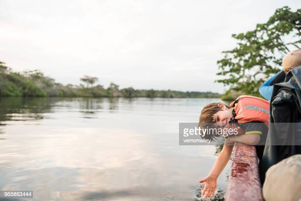 child in the amazon splashing the river off a boat - ecuador stock pictures, royalty-free photos & images