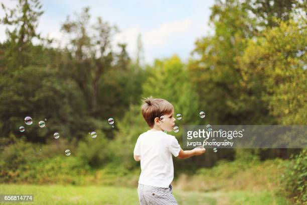 child in the meadow playing with bubbles