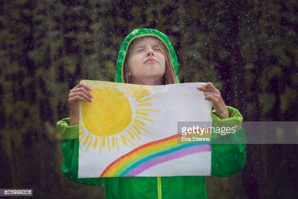 Child in the rain, wishing for sunshine