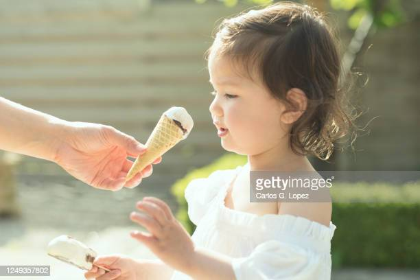 child in white dress holds ice cream and she is offered an ice cream cone by her mom in a sunny spring day - white dress stock pictures, royalty-free photos & images