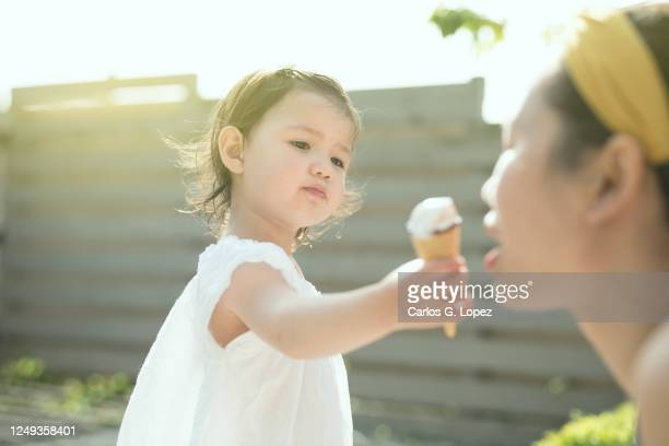 child in white dress shares and ice cream cone with her mother in a sunny day in a garden - white dress stock pictures, royalty-free photos & images