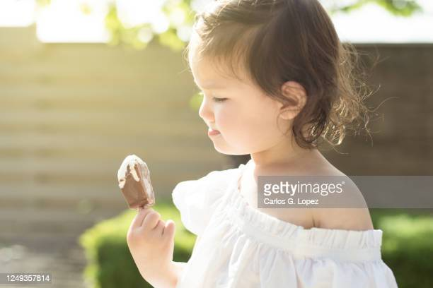 child in white dress tastes ice cream in a garden in a sunny spring day - white dress stock pictures, royalty-free photos & images