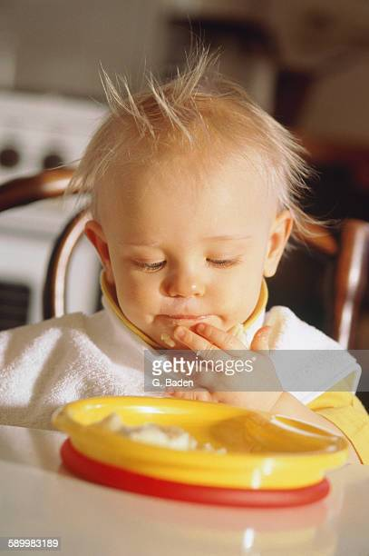 child infant eating from a plastic plate - plastic plate stock pictures, royalty-free photos & images