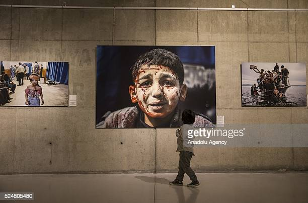 A child inspects Istanbul Photo Awards 2016's photo of the year 'Syrian Children Cry for Help' as Anadolu Agency opens first exhibition showcasing...