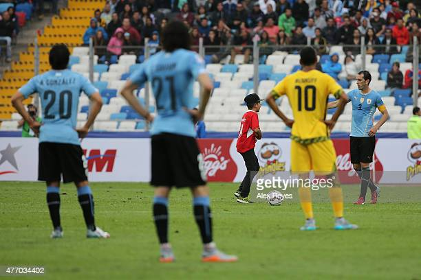 A child invades the pitch during the 2015 Copa America Chile Group B match between Uruguay and Jamaica at Regional Calvo y Bascuñan Stadium on June...