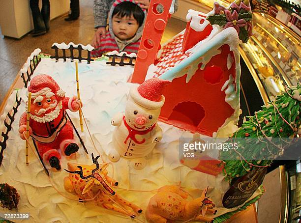 A child is attracted by a huge Christmas cake at a hotel on December 23 2006 in Nantong Jiangsu Province China While Christmas Day is not a public...