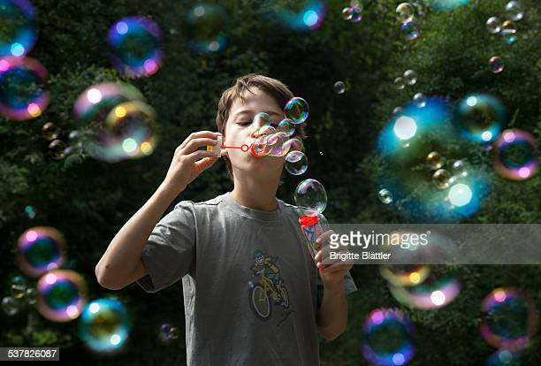 Child is blowing soap bubbles.
