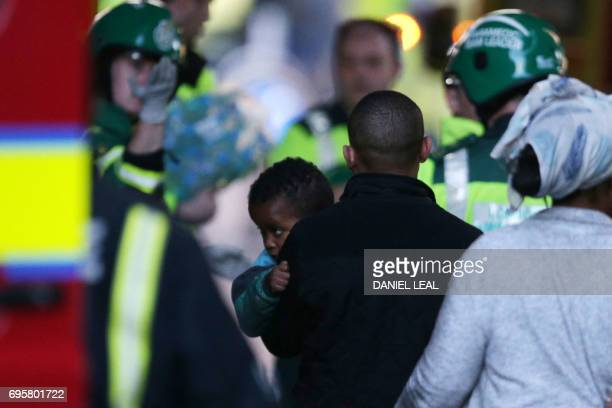 A child is brought to an ambulance within the security cordon as Grenfell Tower is engulfed by fire on June 14 2017 in west London The massive fire...