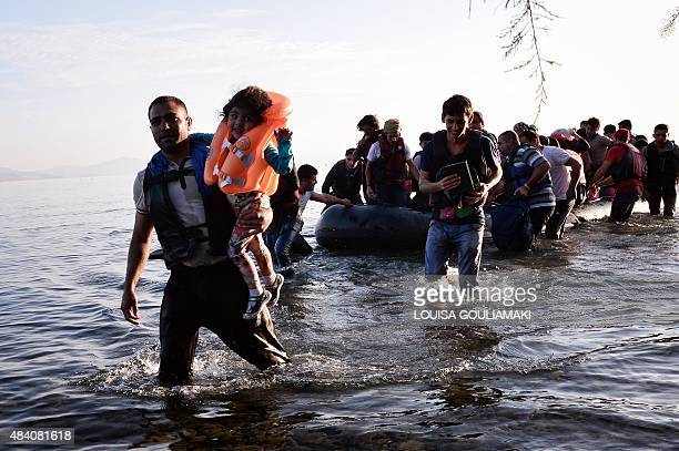 A child is carried as Syrian migrants arrive on an overcrowded dinghy on a beach near the port on the Greek island of Kos on August 15 2015 A ferry...
