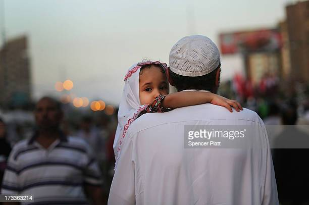 A child is carried down a street by a relative at the base for supporters of ousted president Mohamed Morsi on the third day of Ramadan the sacred...