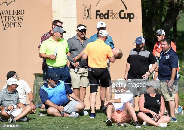 A child is carried off of the 16th hole after being hit by a ball from Matt Kuchar during the second round of the Valero Texas Open at TPC San...