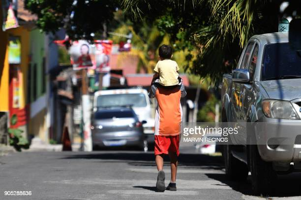 Child is carried on a man's shoulders along a street of San Isidro municipality, Cabanas department, 70 km northeast of San Salvador on January 13,...