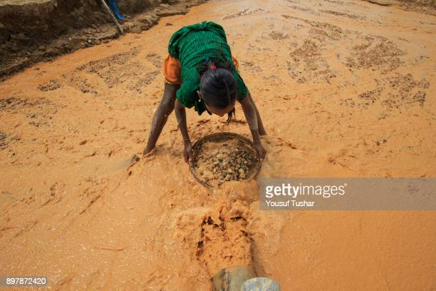 A child is collecting stones at Jaflong Stone Quarry field The crystal clear water of the Piyain River which flows from India through Bangladesh is...