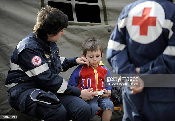 A child is comforted by a red cross rescuer in a refugee camp setup just outside the Abruzzo capital L'aquila epicentre of an earthquake earlier in...