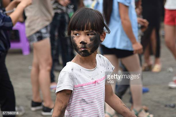 A child is daubed rice ash on face during the Face Painting Festival in Puzhehei Resort of Qiubei County on July 18 2016 in Wenshan Prefecture Yunnan...