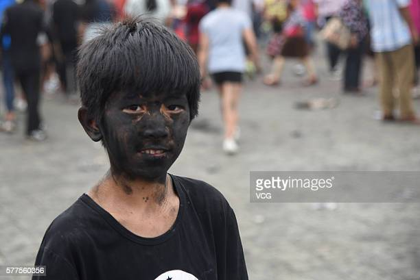 Child is daubed rice ash on face during the Face Painting Festival in Puzhehei Resort of Qiubei County on July 18, 2016 in Wenshan Prefecture, Yunnan...