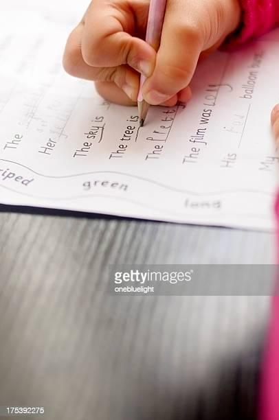 Niño (5-6) está haciendo sus deberes